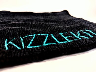 Kizzle Kit's logo in teal on a black microfibre.